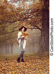 Romantic girl with a bouquet of leaves