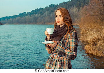 Romantic girl with cup outdoors. Hipster girl drinking tea in the spring in a landscape