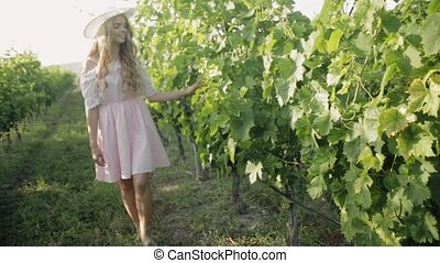 Romantic girl with long hair in the hat touches the leaves of the vine