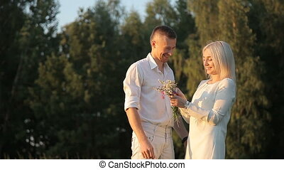 Romantic guy gives a girl a rustic bouquet of wild flowers.