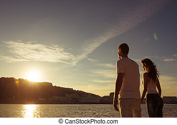 Romantic happy couple in love holding hands on the sunset