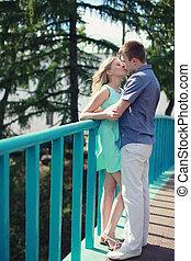 Romantic happy couple in love kiss on the bridge