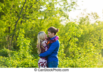 Romantic happy couple in love on nature. Man and woman kissing in summer park.