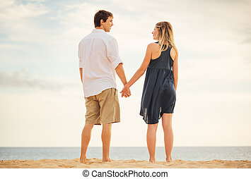 Romantic happy couple on beach at sunset. Smiling holding hands. Man and woman in love