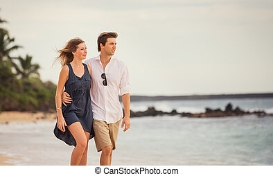Romantic happy couple walking on beach at sunset. Smiling...