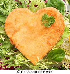 Romantic heart shaped fried golden schnitzel in breadcrumbs served on a bed of fresh leafy green lettuce and basil and garnished with parsley
