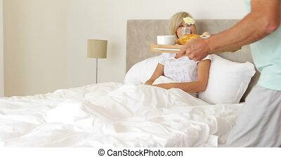 Romantic husband bringing breakfast in bed