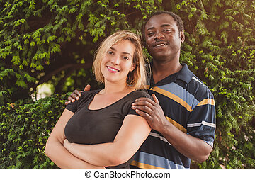 Romantic international young couple in park