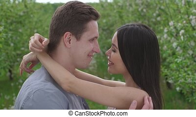 Romantic kiss of young couple in love in orchard - Close-up...