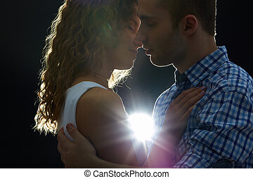 Romantic kiss - Young couple kissing in the dark