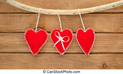 Romantic love composition of red felt hearts on wooden background