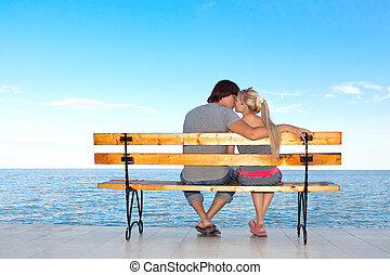 romantic love couple boy and girl kissing on a bench on the beach