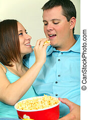 Romantic Male And Female Caucasian Eating Popcorn