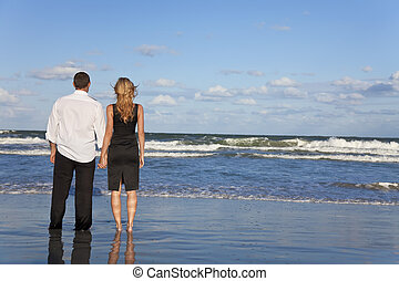 Romantic Man and Woman Couple Holding Hands On A Beach