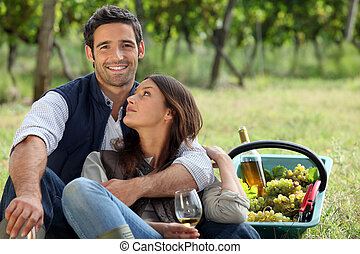 Romantic man and woman picking grapes and drinking wine