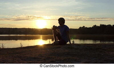 Romantic man drinks tea sitting on a lake bank at sunset in slo-mo