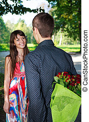 Romantic man giving a bouquet of red roses to his girlfriend