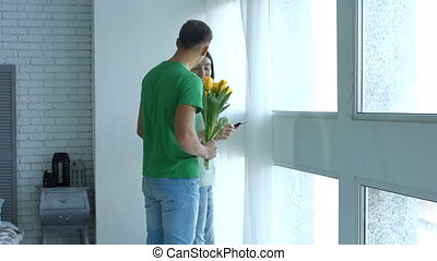 Romantic man giving bunch of flowers to woman