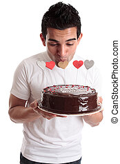 Romantic man kissing heart on a cake