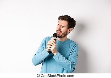 Romantic man singing song in microphone at karaoke, standing over white background