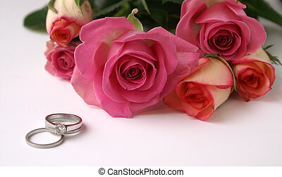 Bridal bouquet of fresh pink roses and entwined platinum wedding rings show a pretty and modern wedding and marriage