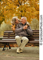 Romantic mature couple sitting in the park in fall