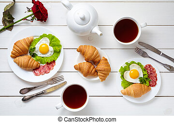 Romantic meal for two with heart shaped eggs, salad, croissants, rose flower and tea on white wooden table background. Food concept of love.