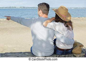 romantic mid adult couple pointing from beach