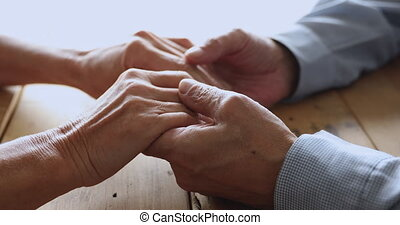 Romantic middle aged married couple stroking hands of each other on table giving support to each other. Loving bonding elderly mature family spouses enjoying sincere trustful conversation at home.