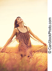 Romantic Model in Sun Dress in Golden Field at Sunset -...