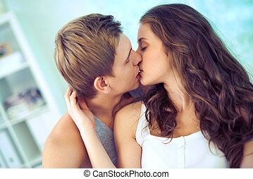 Romantic moment - Young affectionate couple kissing tenderly