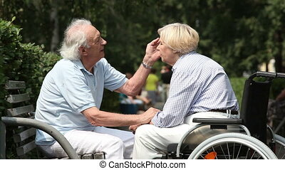 Elderly husband and wife enjoying romantic moments together, woman being in a wheelchair