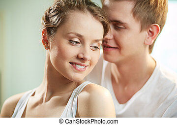 Portrait of smiling young woman being cuddled by loving man