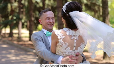 Romantic newly married couple dancing waltz in the park on their wedding day.