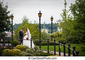 Romantic newlywed couple, groom kissing bride in european park with a town in the background
