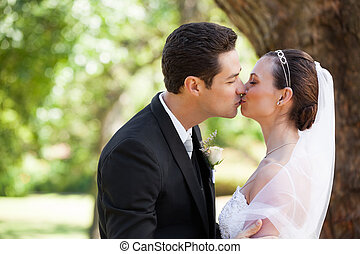 Romantic newlywed couple kissing in park