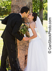 Romantic newlywed couple kissing in