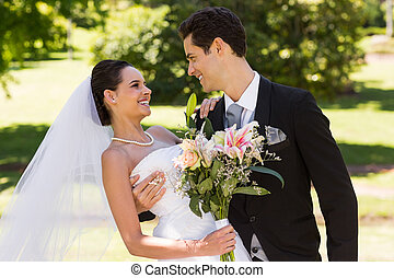 Happy romantic newlywed couple with bouquet in the park