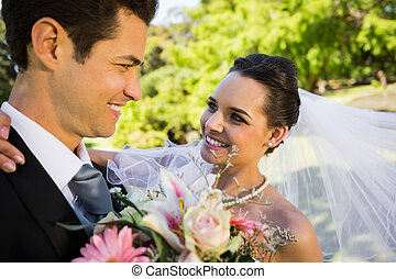 Romantic newlywed looking at each other in park