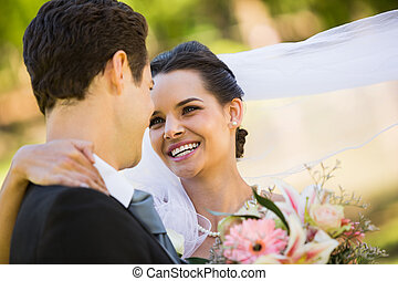 Romantic newlywed looking at each other in park - Close-up...