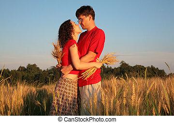 romantic pair embraces on wheaten field