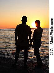 romantic pair looking toward sunset - romantic yong man and...