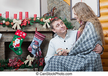 Romantic pair sitting on the chair near fireplace