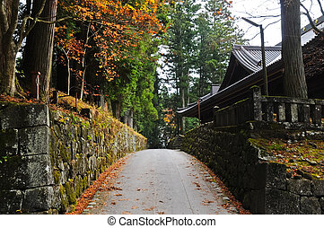 Romantic passage next to an old temple in Japanese Autumn