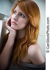 Romantic portrait of a beautiful redhead girl, wearing gray top.