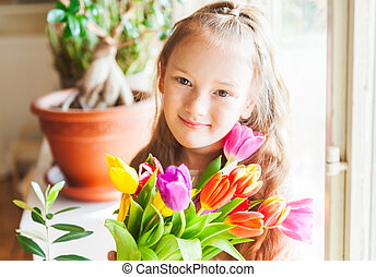 Romantic portrait of adorable little girl with colorful tulips, indoors