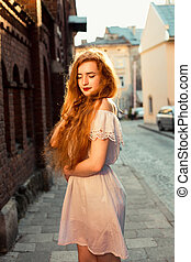 Romantic red haired model with long curly hair wearing white dress posing in evening sunlight