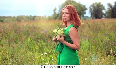 Romantic red-haired young woman in green long dress Walking Through Summer Field Carrying Bouquet Of Flowers