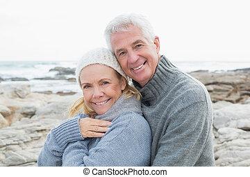 Romantic senior couple on rocky bea