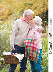 Romantic Senior Couple Outdoors With Picnic Basket By Autumn...